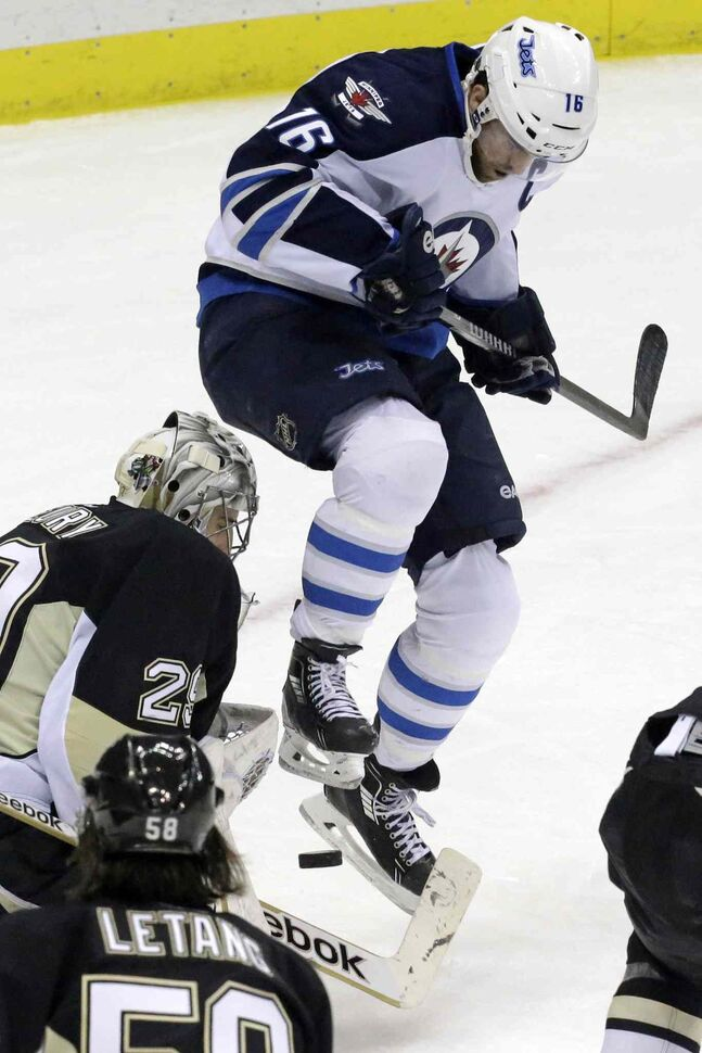 Jets captain Andrew Ladd leaps out of the way of a shot in front of Penguins goalie Marc-Andre Fleury during the first period.