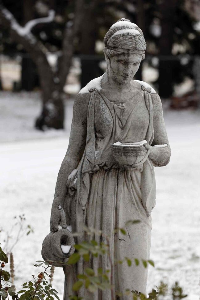A statue stands in the snow in the backyard.