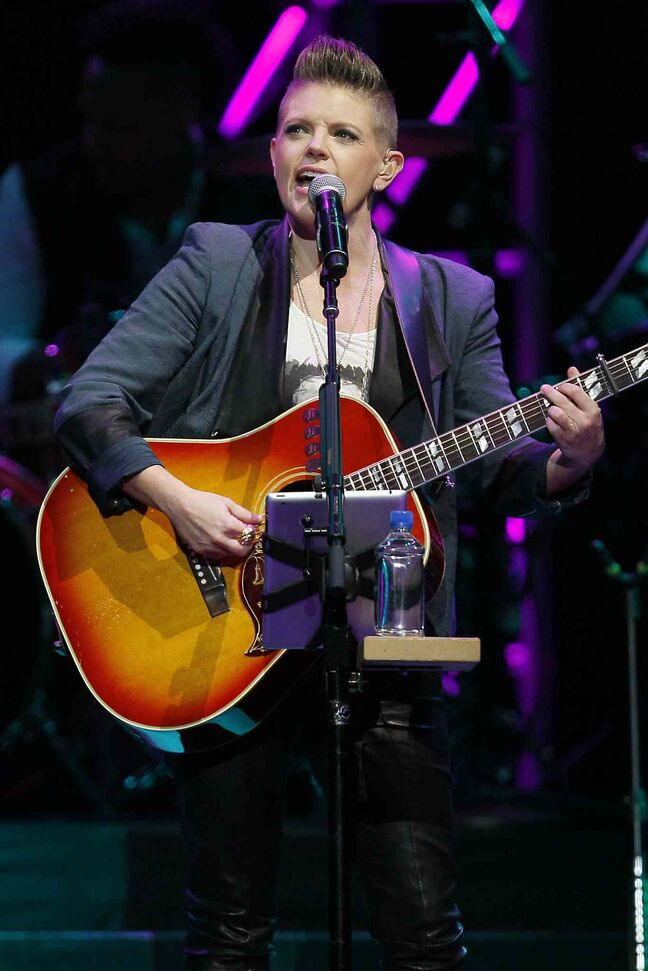 Dixie Chicks lead singer Natalie Maines belts out a song while strumming a guitar.