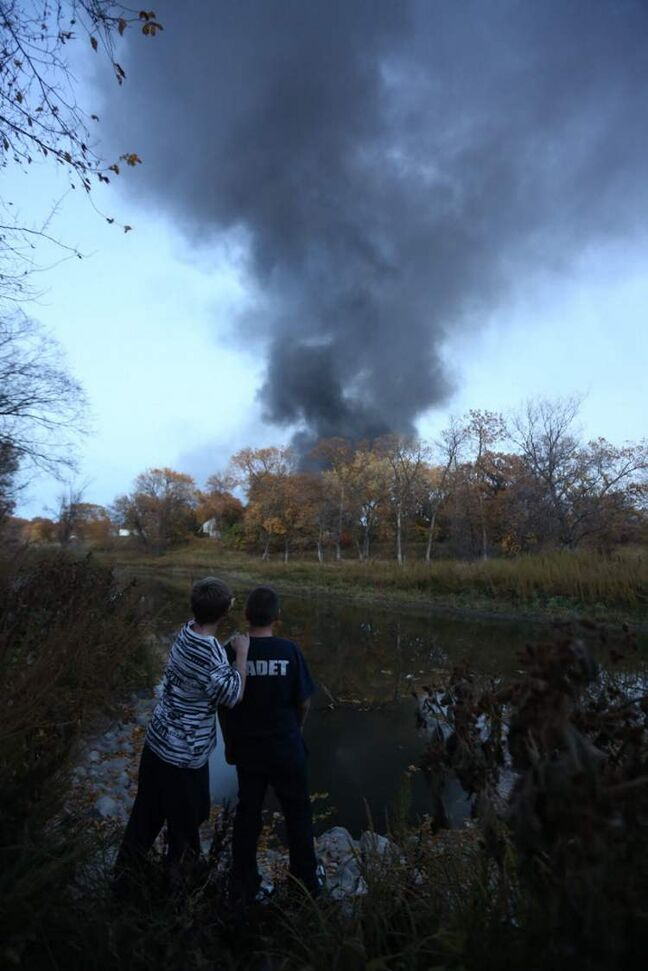 Onlookers watch from a distance as a fire burns.