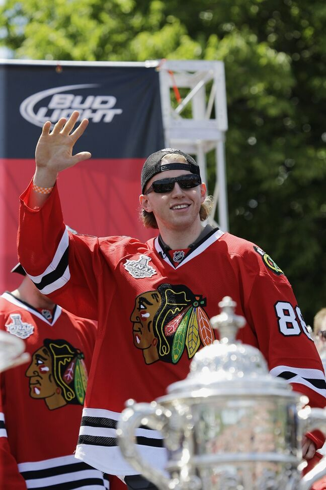 Chicago Blackhawks' Patrick Kane waves to the fans at Grant Park. In the foreground is the Clarence S. Campbell bowl, awarded to the Western Division champions.