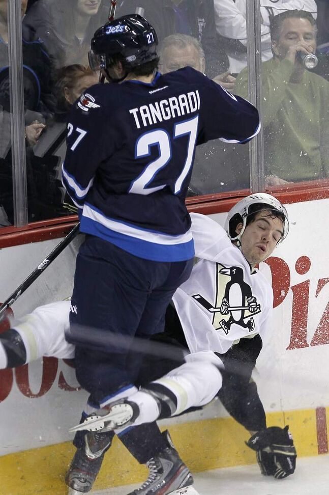 Winnipeg Jets' Eric Tangradi (27) hits Pittsburgh Penguins' Simon Despres (47) during first period NHL action in Winnipeg on Friday, February 15, 2013. 
