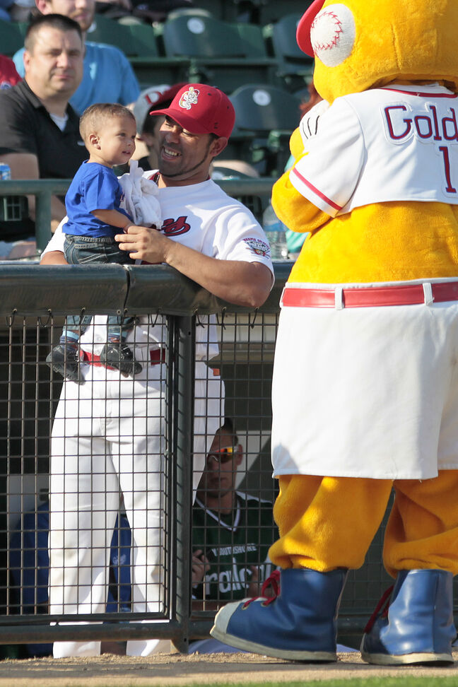 Winnipeg Goldeyes' mascot plays with Goldeyes catcher Luis Allen and baby at the All-Stars Skills Competition.