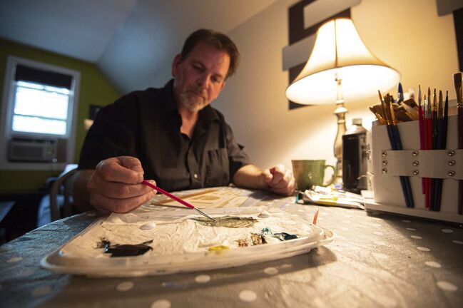 Artist Ken Hodgert works on a painting of Winnipeg's Union Station in his apartment. He sells paintings of businesses and restaurants, many from yesteryear, under the banner Underground Nostalgia. (Mike Sudoma / Winnipeg Free Press)</p>