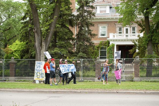 Protesters picket outside the 110-year-old mansion at 514 Wellington Cres. on June 8. (Sasha Sefter / Winnipeg Free Press)