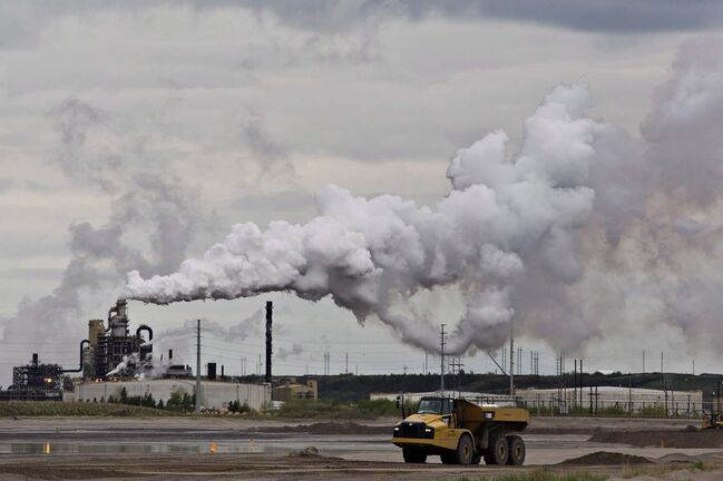 A dump truck works near the Syncrude oil sands extraction facility near the city of Fort McMurray, Alta., on June 1, 2014. The parliamentary budget office says most Canadian households will receive more money back from the federal government's carbon-tax scheme than it will cost them. The assertion is contained in a report published by the PBO this morning, nearly four months after a majority of Canadian voters cast their ballots in favour of parties that favoured a carbon tax. THE CANADIAN PRESS/Jason Franson</p>