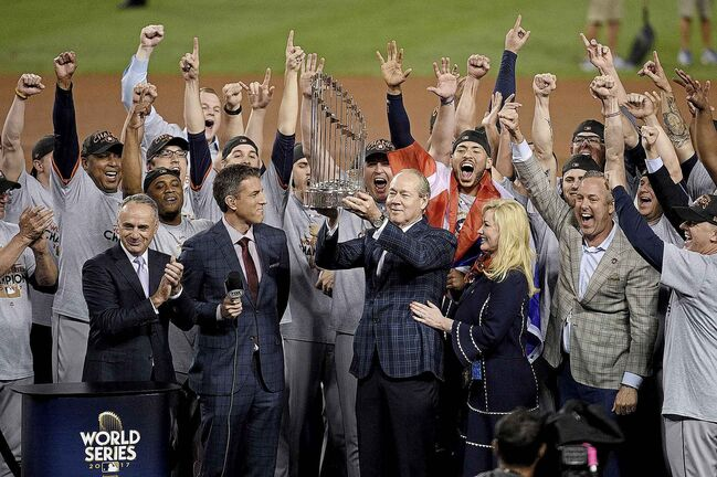 Houston Astros owner and chairman Jim Crane hoists the Commissioner's Trophy after the Astros cheated to beat the Los Angeles Dodgers in the 2017 World Series. (Kevork Djansezian / Getty Images)