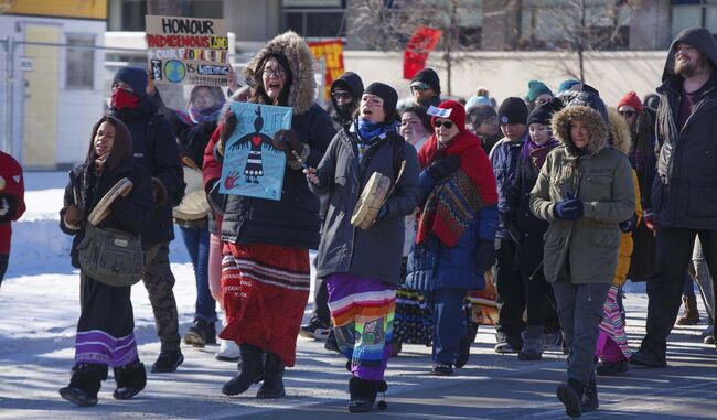 "Holding a sign that says, ""Water is life,"" Brielle Beardy-Linklater, a local activist, walks with drummers over the lunch hour in support of the Wet'suwet'en hereditary chiefs blocking construction of a natural gas pipeline in northern B.C. (Mike Deal / Winnipeg Free Press)						</p>"