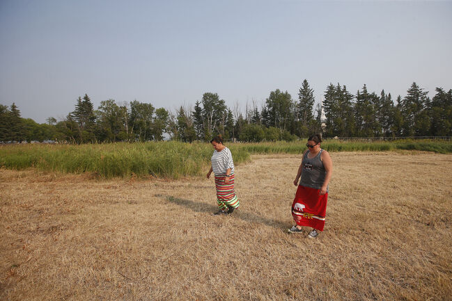 Councillors Lin Dorie (left) and Erin Dorie walk through a field where they performed a smudge ceremony in preparation for a search for unmarked graves on the site of a former residential school in Sagkeeng, (John Woods / Winnipeg Free Press)