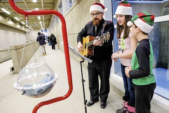 Captain Josh Howard (left) sings Christmas carols with his kids Abigail (middle) and Julian (right) at the Superstore on Portage Ave. to help the Salvation Army reach its goal of $385,000 by Christmas Day. (Daniel Crump / Winnipeg Free Press)