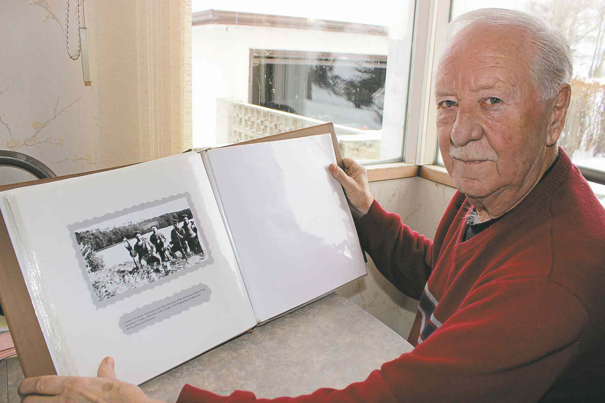 Neepawa historian and writer Cecil Pittman looks at scrapbook containing a photo of Titanic victim Leonard Hickman on a duck-hunting expedition with a group of local men.