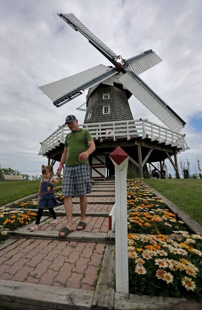 Jazmyn Barkman, 3, and her father, Darrell, outside the windmill at the Steinbach Pioneer Days at the Steinbach Mennonite Heritage Village, Sunday. (TREVOR HAGAN / WINNIPEG FREE PRESS)