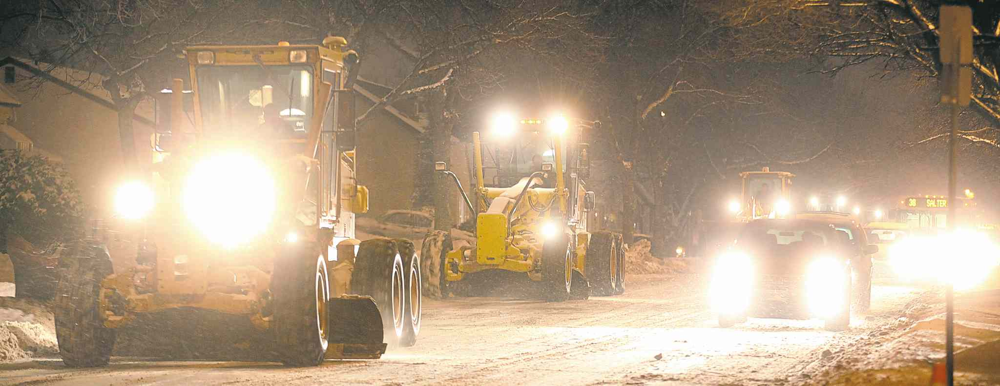 Graders and plows move along Leila Avenue near Salter Street Tuesday evening during the city's latest snow-clearing operation.