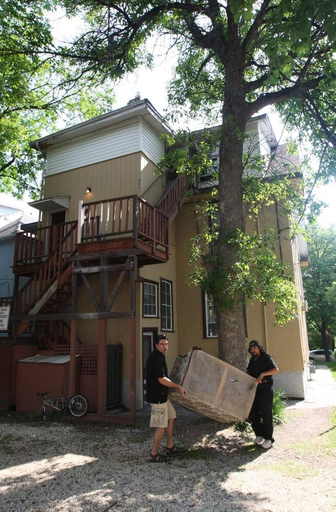 Landlord Steve Tait (left) moves furniture from his Furby Street rooming house with a tenant. (JOE BRYKSA / WINNIPEG FREE PRESS)