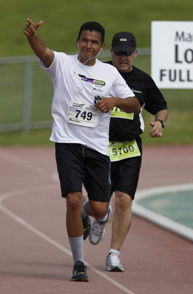 Wab Kinew nears the finish line of the full marathon at the University of Manitoba during the Manitoba Marathon.