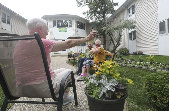 RUTH BONNEVILLE / WINNIPEG FREE PRESS</p><p>LOCAL - care homes</p><p>Joyce Church, a resident of Thorvaldson Care Centre, reaches out to give her daughter, Janis Brackman and her son-in-law Alan Brackman, a distance hug in the outdoor patio space at her residence on Tuesday.</p><p>What: Family members can now visit their loved ones in personal care homes (COVID-19 restrictions are changing).</p><p>See Gabby's story.</p><p>.June 23, 2020</p>