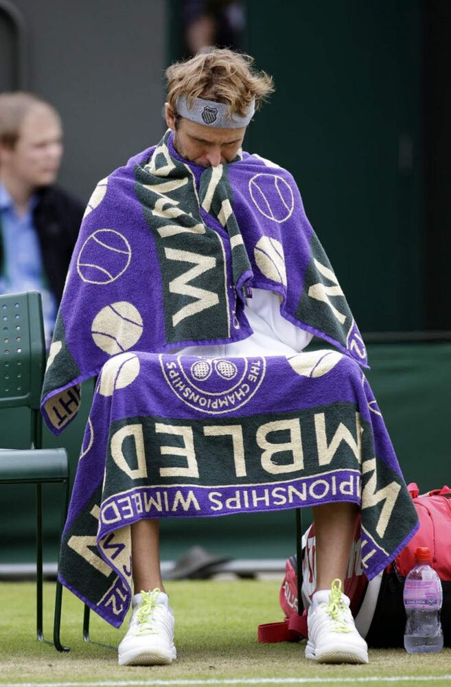 Mardy Fish of the United States waits as Jo-Wilfried Tsonga of France is checked by a trainer during a fourth round singles match at the All England Lawn Tennis Championships at Wimbledon, England. (AP Photo/Sang Tan)