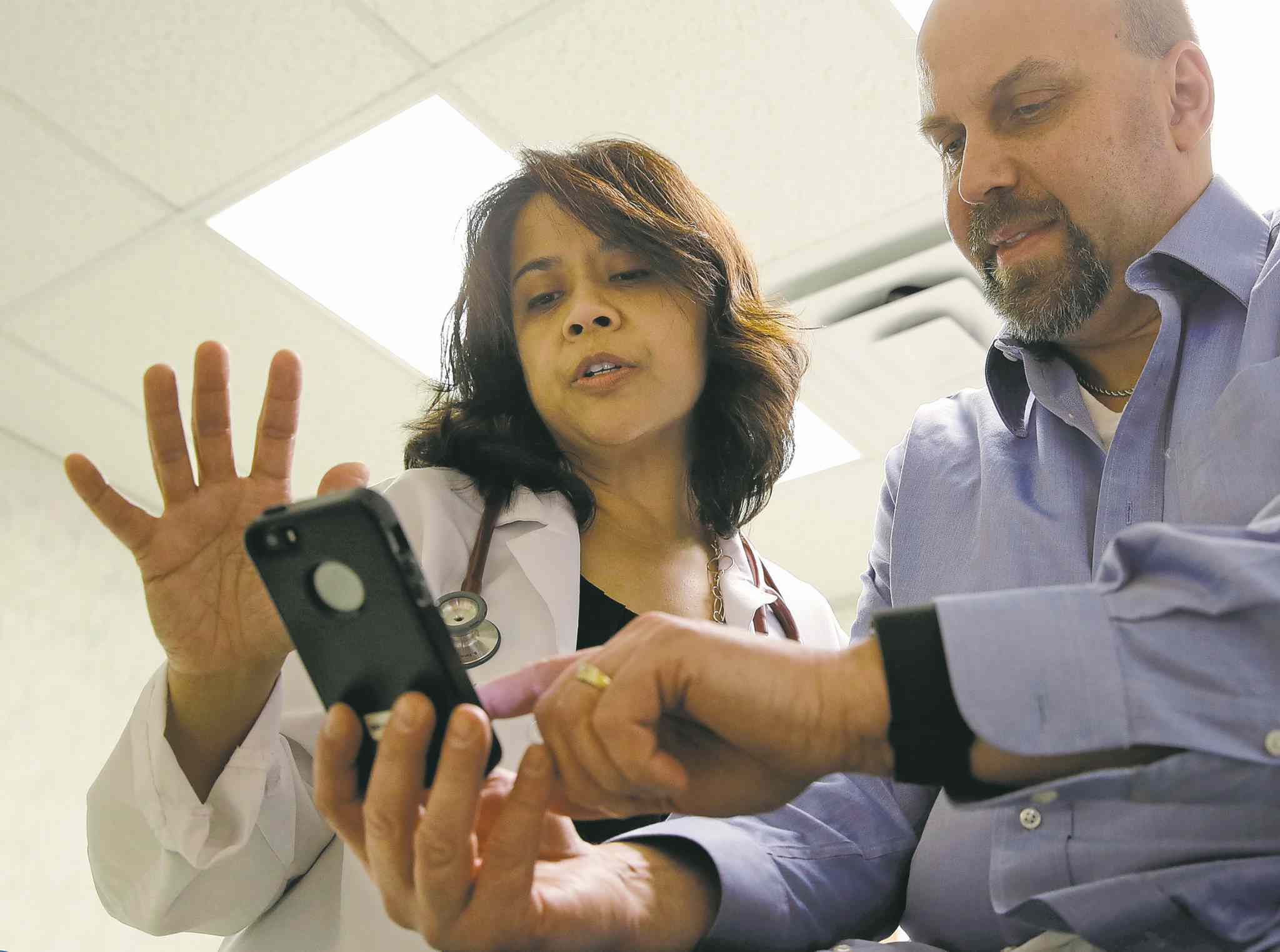 Dr. Sarah Timmapuri eyes a smartphone synchronized to a Fitbit Surge worn by patient Gary Wilhelm.