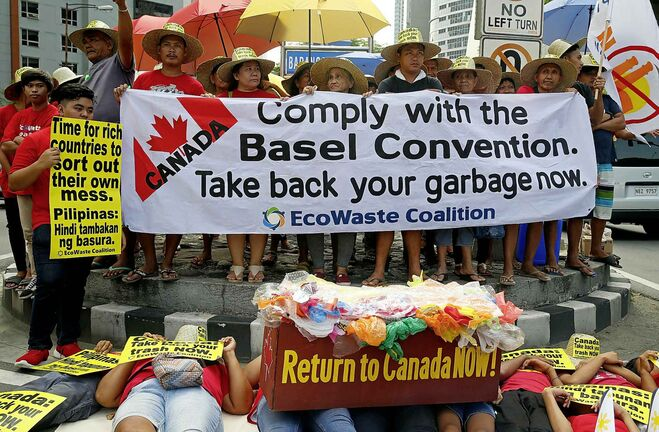 Environmentalists stage a die-in protest in Manila, Philippines last week to demand Canada take home 69 shipping containers of trash that had been mislabelled and illegally shipped to the Philippines as recyclable material. (Bullit Marquez / The Associated Press files)