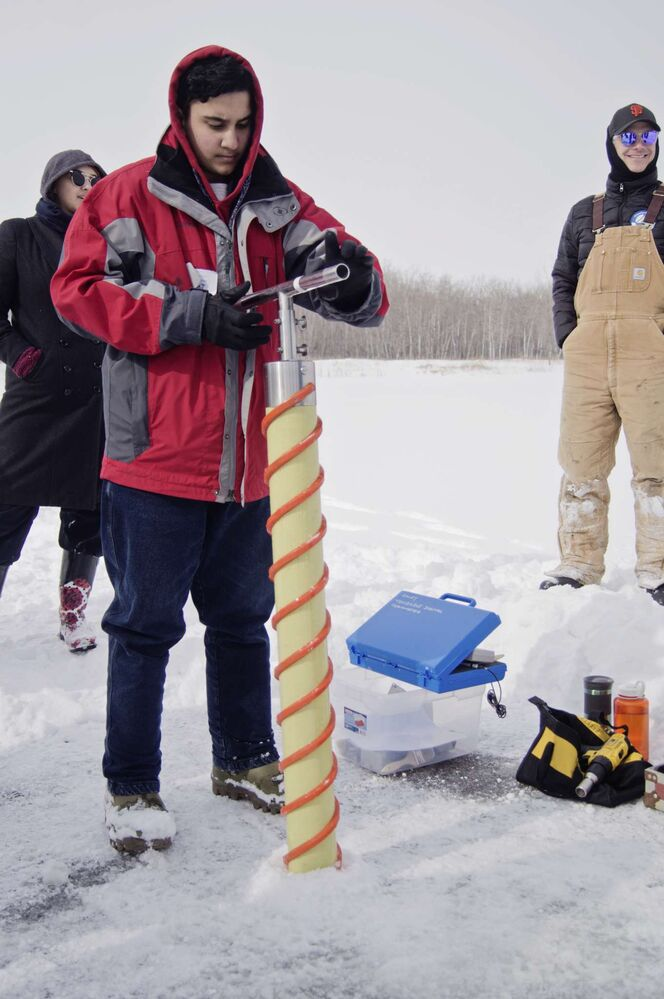 Manraj Bambra drills into the ice at FortWhyte Alive during Arctic Science Day.  (Danielle Da Silva - Sou'wester)