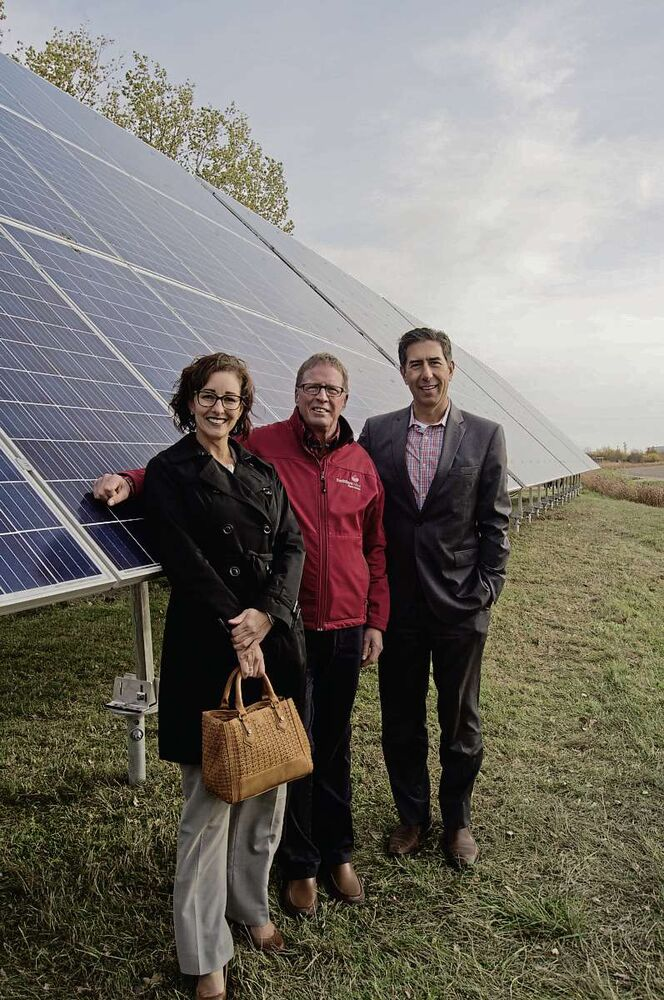 Colleen Kuruluk, manager of the PowerSmart program at Manitoba Hydro; Bill Elliott, president and CEO of FortWhyte Alive; and Ron Seftel, CEO of Bullfrog Power, pose for a photo next to FortWhyte Alive's new 60 kilowatt solar plant. (Danielle Da Silva - Sou'wester)