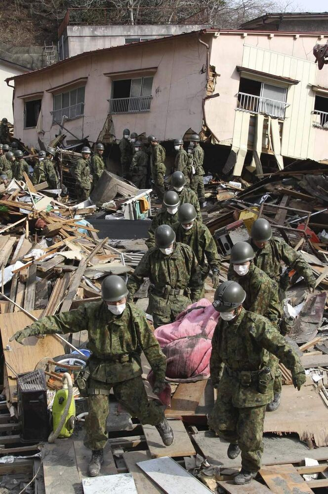 Self-Defense Force members carry the body of a victim in Kamaishi, northern Japan, Monday, March 14, 2011, three days after a powerful earthquake-triggered tsunami hit the country's east coast. (AP Photo/The Yomiuri Shimbun, Daisuke Uragami)