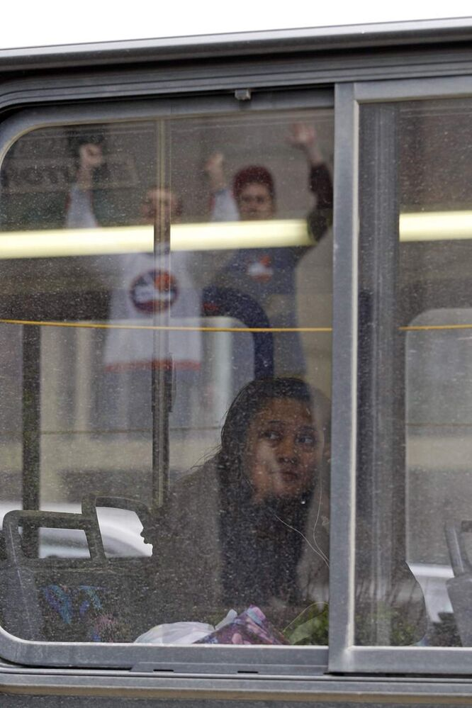 NHL comes back to Winnipeg - fans  at Portage and main serenade transit bus rider
