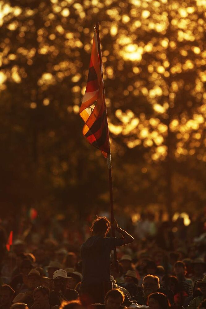 A spectator holds a flag as the sun sets. (John Woods / Winnipeg Free Press)
