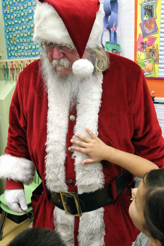 Besides the impromptu hugs, Santa had kids checking to see if his belly shook like a bowl full of jelly during his visit to the Black River Anishinabe School.