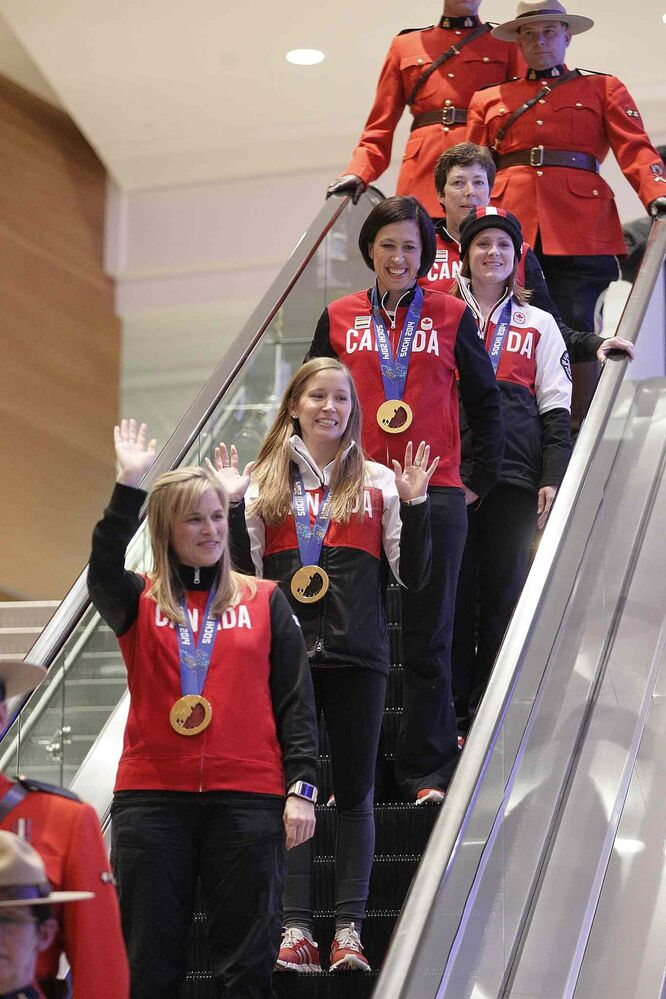 Olympic curling gold medalists Jennifer Jones (skip), Kaitlyn Lawes (third), Jill Officer (second), Dawn McEwen (lead), Kirsten Wall (alternate) and their coach Janet Arnott return to hundreds of family and supporters at the Winnipeg Airport Monday. (John Woods / Winnipeg Free Press)