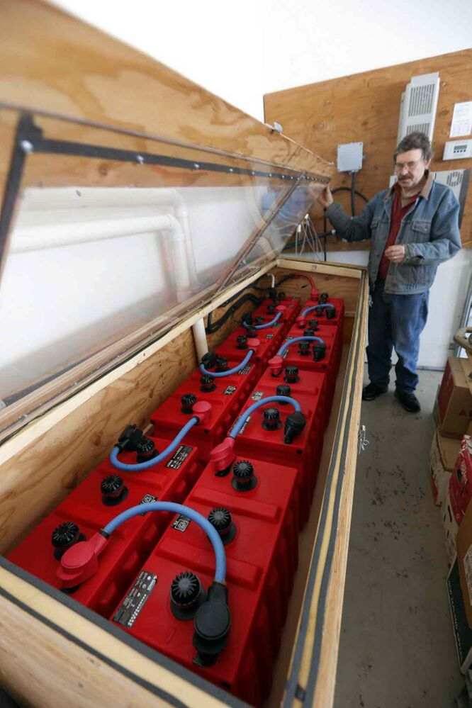 Will Eert with batteries that store solar energy from his two panels. (KEN GIGLIOTTI / WINNIPEG FREE PRESS)