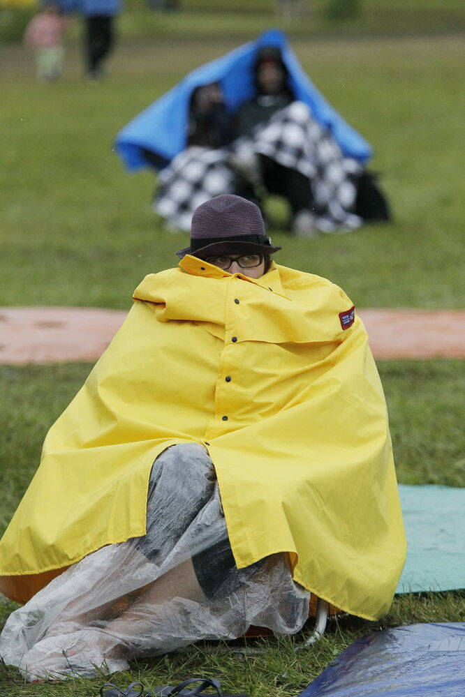 A Folk Fest attendee huddles up on a rain coat on a very wet final day of the event Sunday, July 13, 2014.  (Winnipeg Free Press)