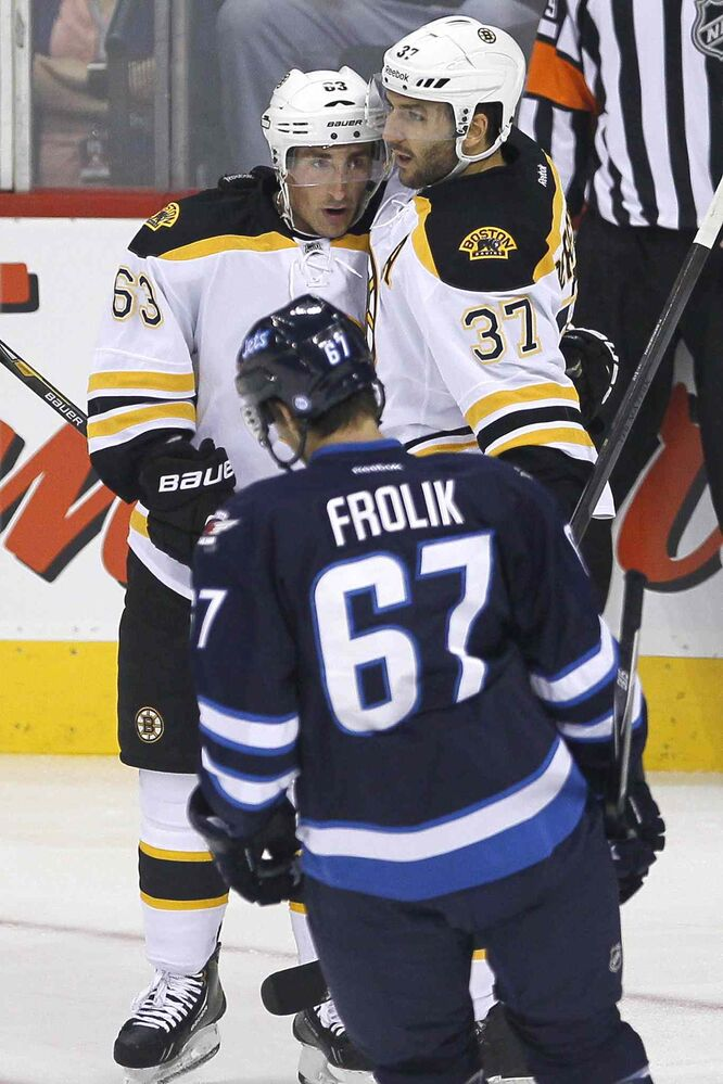 Boston Bruins' Brad Marchand (63) and Patrice Bergeron (37) celebrate Bergeron's goal as Michael Frolik looks on during the first period.