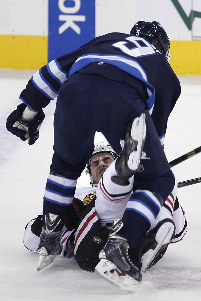 Winnipeg Jets' Evander Kane (9) takes down a member of the Chicago Blackhawks during the first period.