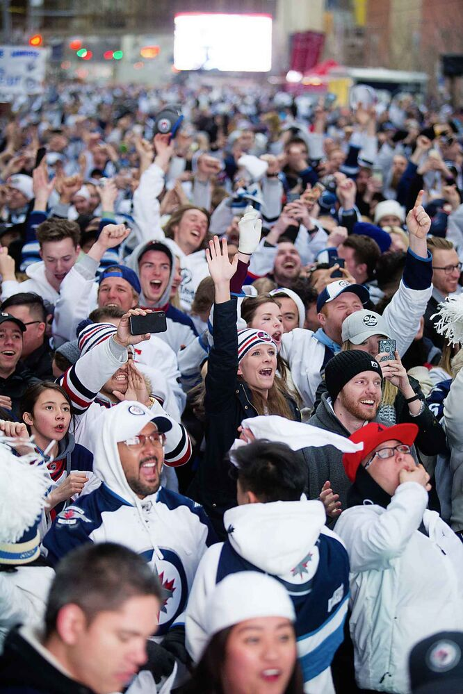 MIKAELA MACKENZIE / WINNIPEG FREE PRESS<br>The crowd goes wild as the Jets score the first goal of the game at the Jets whiteout party on Donald St.<br>