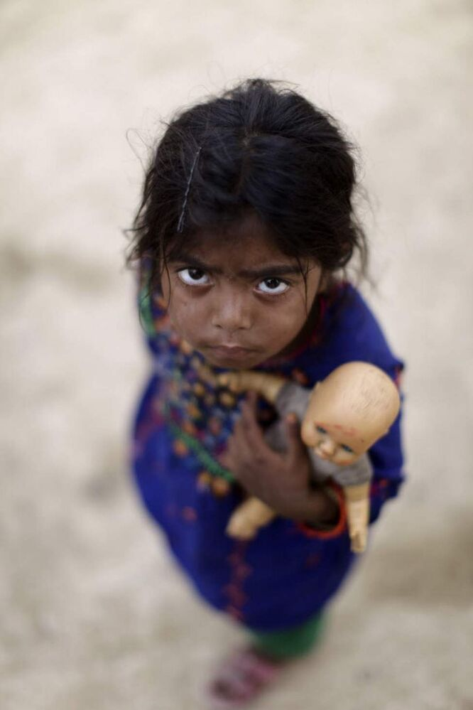 Pakistani girl Saima Hashim, 5, whose family was displaced by 2010 floods from a village in Pakistan's Sindh province, looks up while holding her doll, in a slum on the outskirts of Islamabad, Pakistan. (AP Photo/Muhammed Muheisen)