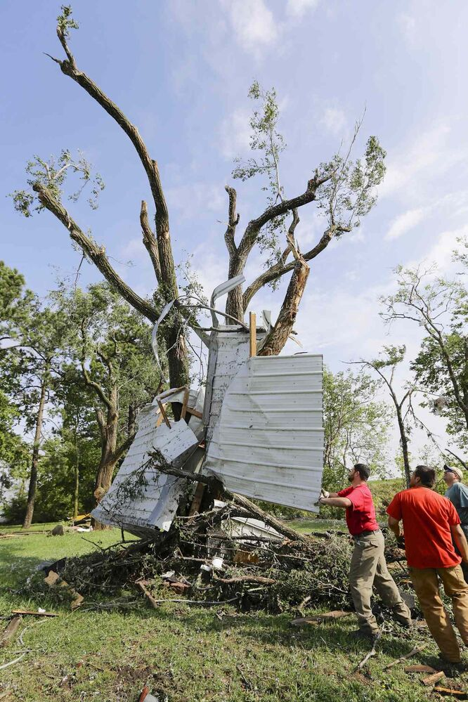 Residents try to free a house panel lodged against a tree in a tornado Friday in Bennet, Neb.. Powerful storms crawled into the Midwest on Friday, also dumping heavy snow in South Dakota and threatening dangerous thunderstorms from Oklahoma to Wisconsin.  (Nati Harnik / The Associated Press)