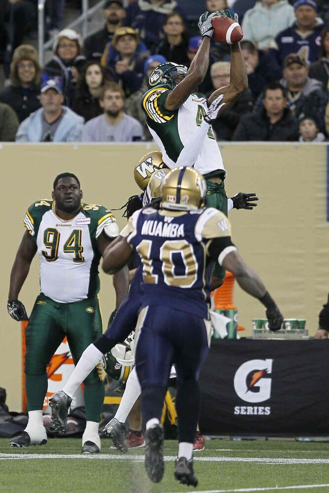Edmonton Eskimos' Adarius Bowman goes up for the pass as Winnipeg Blue Bombers Henoc Muamba looks on during the first half. (John Woods / The Canadian Press)