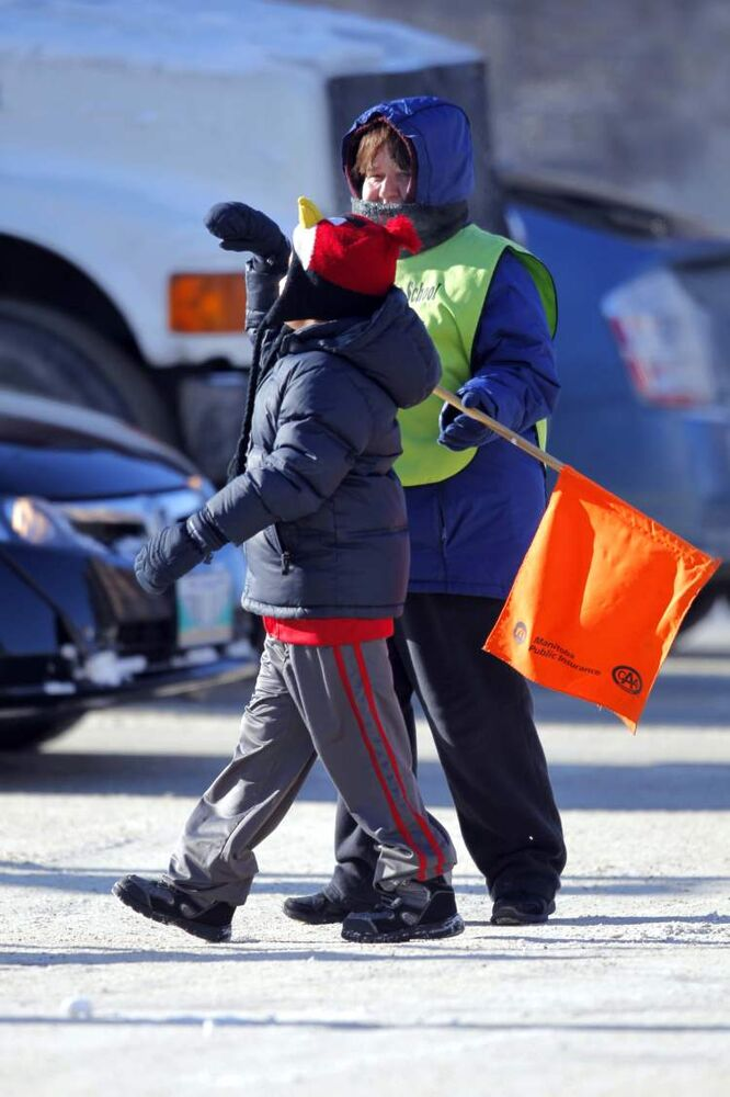 School crossing guard Donna Adams ensures a student crosses safely at the intersection of Sargent Avenue and Balmoral Street Monday. (BORIS MINKEVICH / WINNIPEG FREE PRESS)