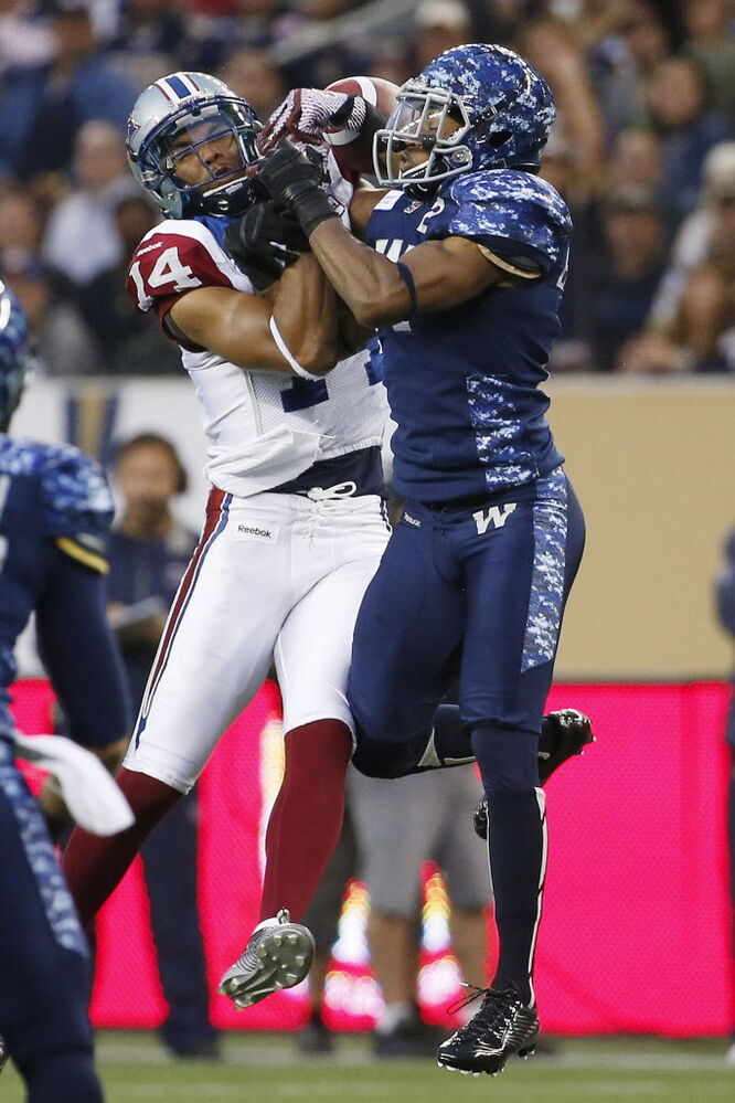 Montreal Alouettes' Brandon London (14) and Winnipeg Blue Bombers' Matt Bucknor (2) go up for the pass.