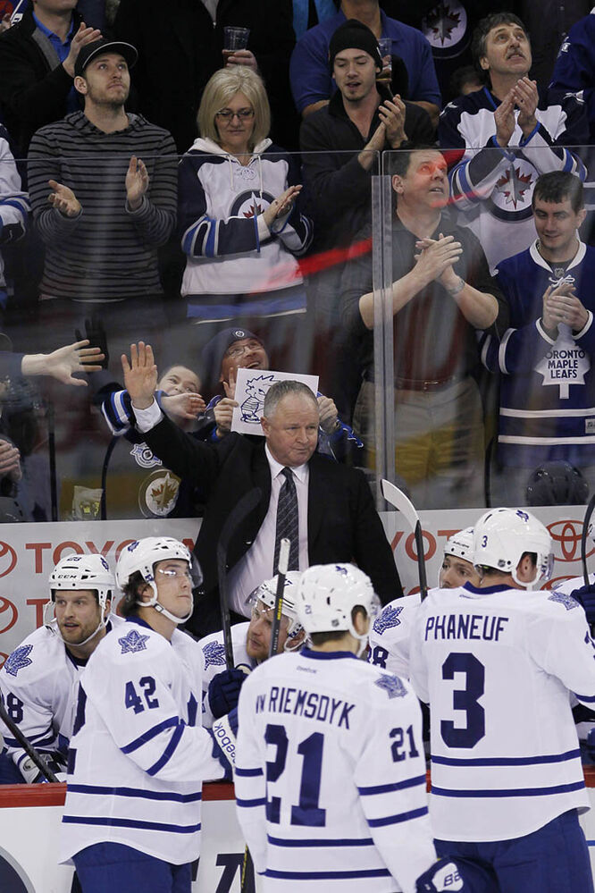 Toronto Maple Leafs head coach Randy Carlyle, who played and coached in Winnipeg for 18 years, waves to the Winnipeg Jets fans as they give him a standing ovation during the first period at MTS Centre in Winnipeg Thursday night.