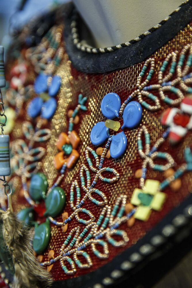 A modern usage of computer components within beadwork on clothing in a closeup of a piece by Barry Ace, Mino-bimaadiziwin (The Way of the Good Life), 2017 (mixed media textile).<br>