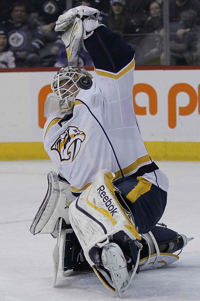 Nashville Predators' goaltender Carter Hutton (30) saves Winnipeg Jets' Blake Wheeler's (26) shot but the puck goes off his leg and into the goal — the Jets' third during second period in Winnipeg on Tuesday.