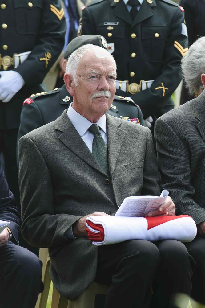 Don Gibbons, grand-nephew of Private Sidney Halliday, holds the Canadian flag presented to him during the ceremony at the burial of eight Canadian First World War soldiers from the 78th Battalion at the Caix British Cemetery in Caix, France on 13 May 2015. This burial was the largest of its kind since the Canadian Armed Forces Casualty Identification program started in 2006. (Corporal Jordan Lobb, Canadian Forces Joint Imagery Center, Ottawa)