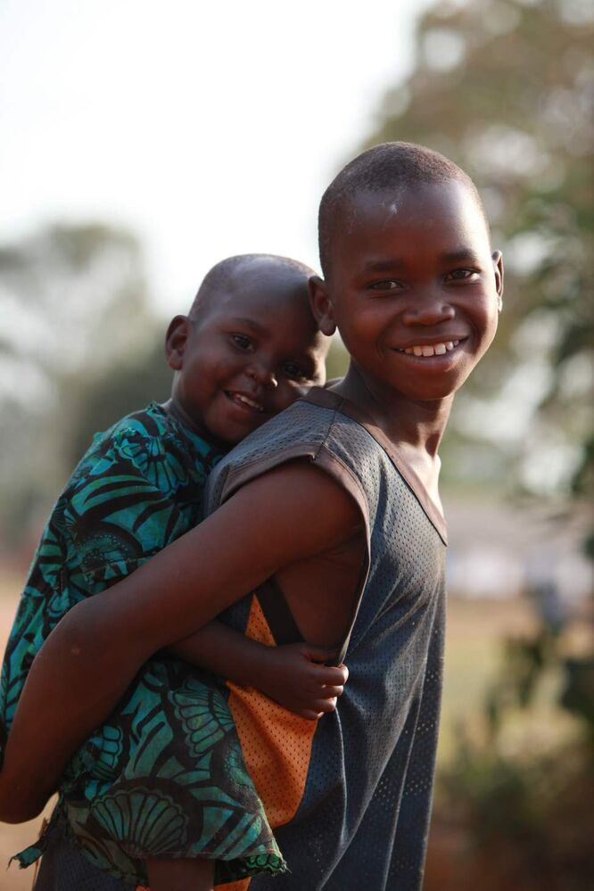 A young boy carries his little baby sister on his back in a village near Gulu in Uganda Africa.  Many of the children in this village are orphaned due to war and disease. Watch Ruth's video feature here: http://wfp.to/8H0 Feb 2013 Ruth Bonneville / Winnipeg Free Press