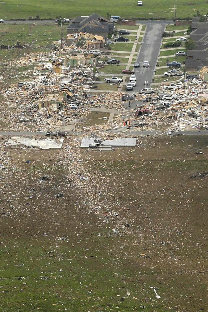 A trail of debris, bottom, leads along the path of a tornado-devastated neighborhood in Vilonia, Ark., Monday, April 28, 2014, after a tornado struck the town late Sunday.