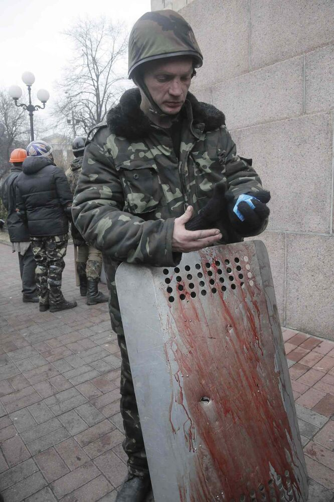 An activist holds a shield with a bullet hole, covered with the blood of his comrade killed in clashes with police in Kyiv's Independence Square on Thursday. Deadly clashes between police and protesters in Ukraine's capital have shattered the brief truce Thursday. (Efrem Lukatsky / The Associated Press)