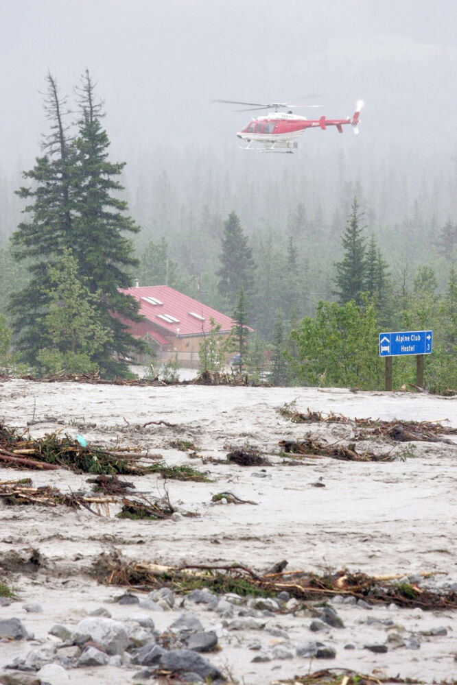 Debris and water pours across the Trans-Canada Highway near Canmore.