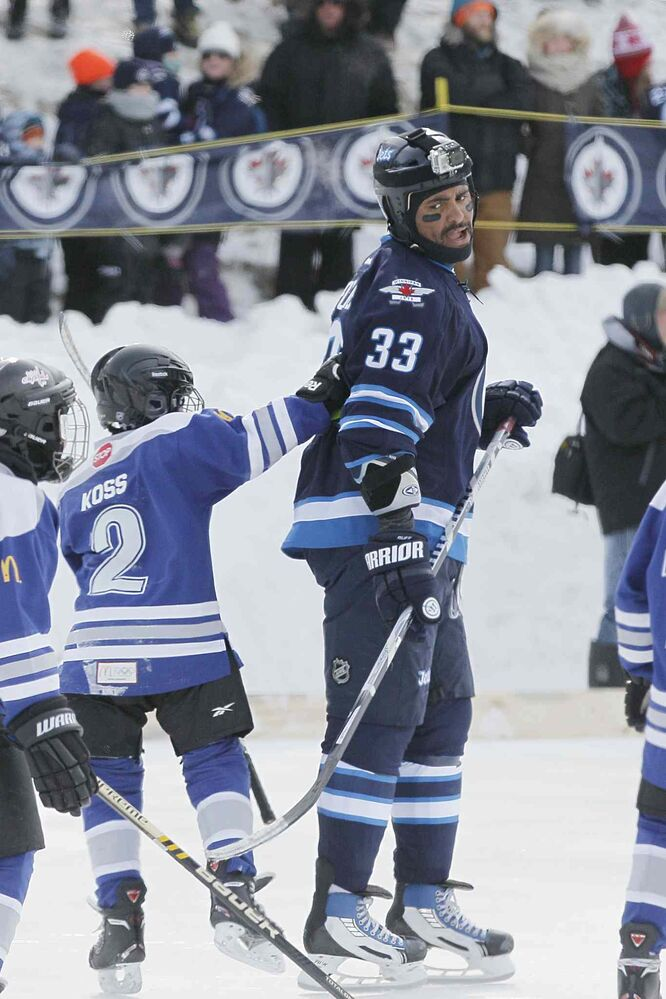 Jets forward Dustin Byfuglien (33) gets checked by CJ Koss (2) of the Portage Atom A's at The Forks on Sunday. (John Woods / Winnipeg Free Press)