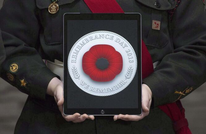 A tablet displays a digital poppy Canadians can post on social media. (Adrian Wyld / The Canadian Press files)
